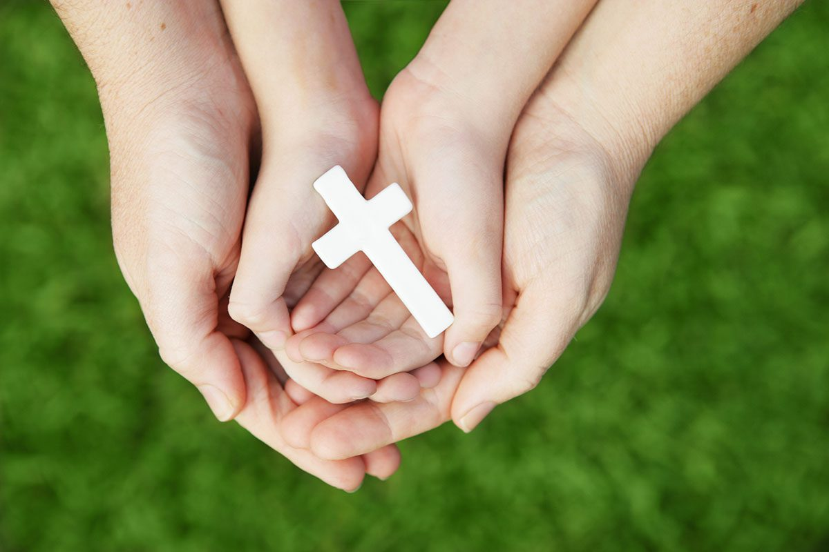 A Small Cross being held in adult and child hands